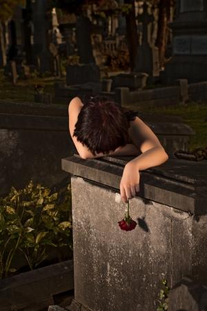 mourn: Notte colpo di una donna gotica giovane piangere su una tomba