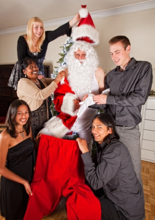 Happy family helping their father getting dressed in his santa claus costume Stock Photo - 15572409