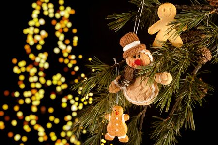 Real and fake gingerbread men hanging in a christmas tree photo