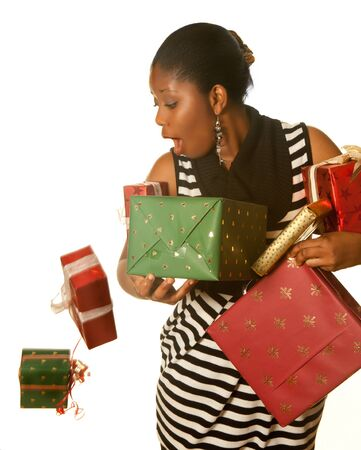dropping: Pretty african girl holding her christmas presents and dropping two