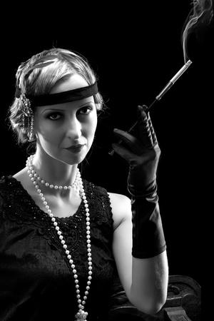 flapper: Mujer en vestido flapper en estilo años veinte fumando un cigarrillo