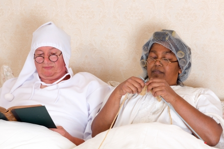Retired couple reading and knitting in bed in vintage clothing