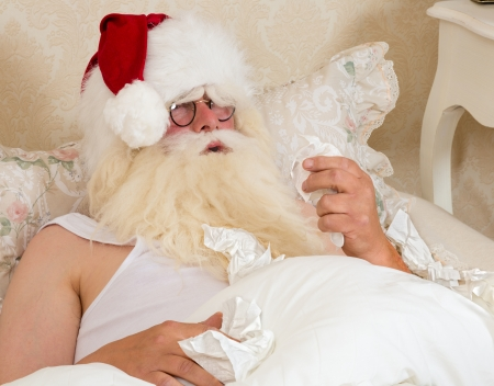 sneezing: Sneezing Santa Claus lying in bed with the flu or a cold Stock Photo