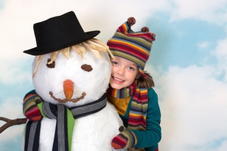 Happy little girl hugging her lifesize snowman photo