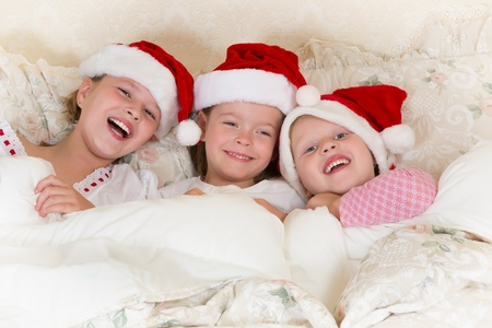 Laughing little girls in bed with santa hats on photo