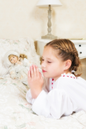 Vintage little girl saying her prayers in her bedroom, beside her antique doll photo