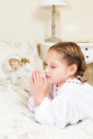 niño orando: Vintage niña pequeña diciendo sus oraciones en su dormitorio, al lado de su muñeca antigua Foto de archivo
