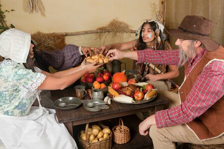 wampanoag: Reenactment scene of the first Thanksgiving Dinner in Plymouth in 1621 with a Pilgrim family and a Wampanoag Indian