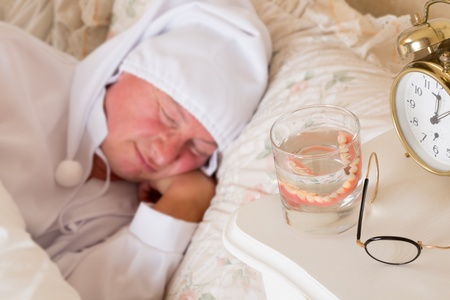 Vintage scene of a sleeping man with his false teeth in a glass of water Stock Photo - 15831104