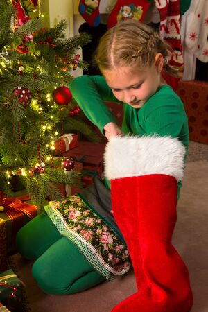 little girl looking deep into her christmas stocking stock photo 15831220 - Girl Christmas Stocking