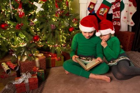 Two little girls reading in a book near the christmas tree photo