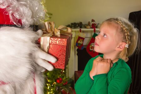 Little blonde girl receiving a red present from Santa Claus photo