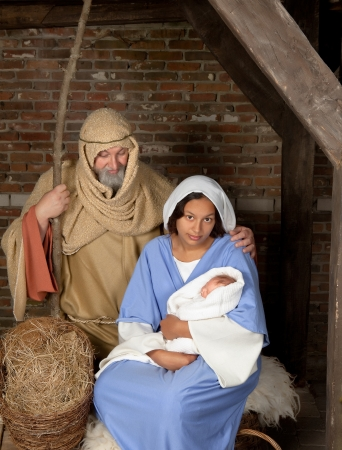 holy family: Live Christmas nativity scene reenacted in a medieval barn Stock Photo