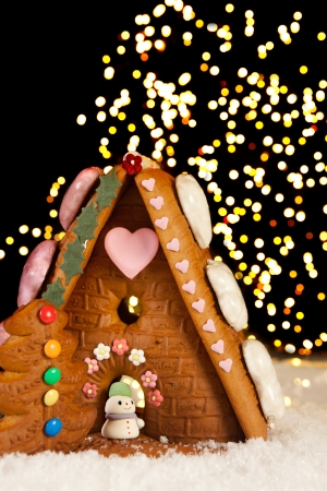 Gingerbread house against a background of christmas tree lights photo