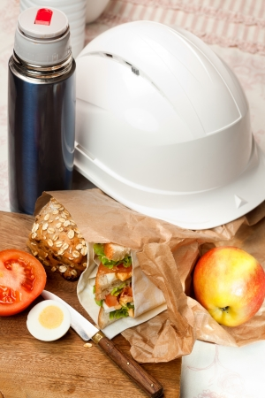 Construction worker's helmet and sandwich lunch bag photo