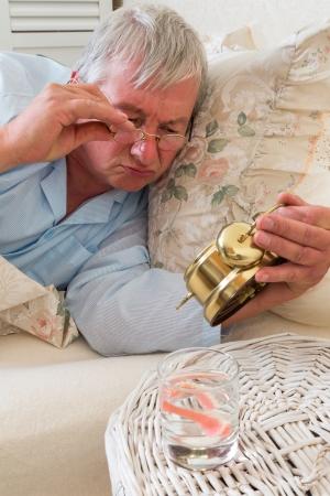 false teeth: Older man waking up and checking his alarm clock Stock Photo