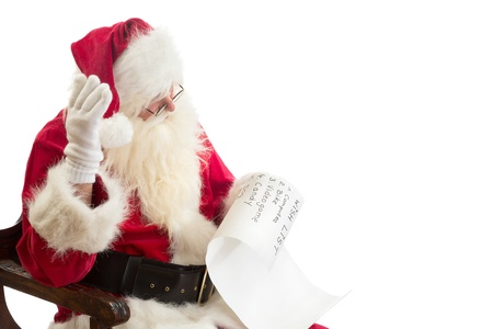 wish list: Santa Claus is surprised about the expensive presents on a wish list Stock Photo