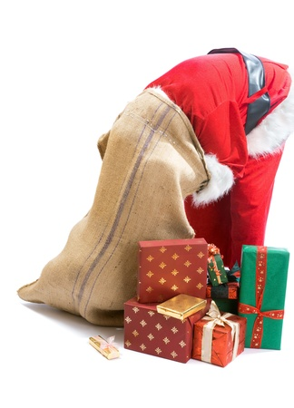 Santa Claus looking for a gift and putting his head in the gifts bag photo