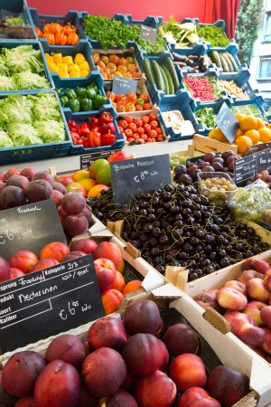 cherry varieties: Colorful display of fruits and vegetables in a European greengrocers shop with price tags in euros and no brand names