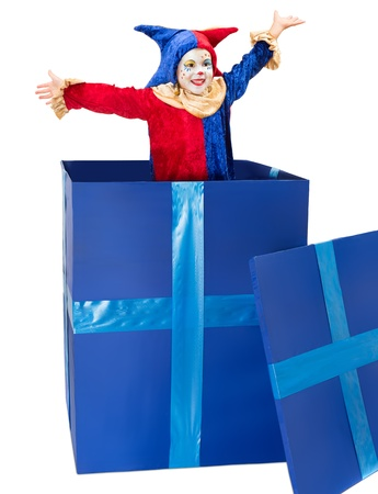 clown circus: Little girl dressed as a clown playing surprise party in a big blue box Stock Photo