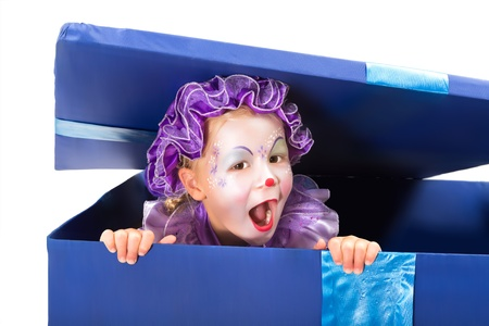 Little four year old popping out of a surprise box in clown disguise photo