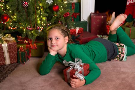 Adorable girl lying in front of the christmas tree with her present photo