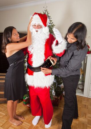 Son and daughter helping their father getting dressed in his santa claus costume Stock Photo - 16054494