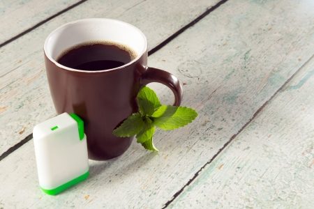 sweetening: Little white box of stevia tablets as sweetener for a mug of coffee