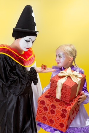 Happy little clown with big presents and sad pierrot with a small gift photo