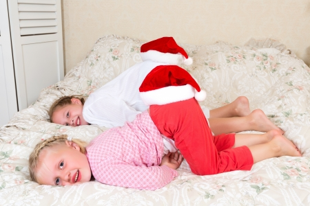 Two funny girls in pyjamas wearing their santa hats on the wrong place Stock Photo - 16104055