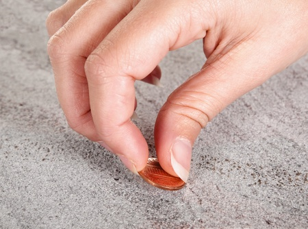 copper coin: Female hand finding a copper cent or money on a pavement Stock Photo