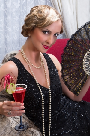 Elegant woman in twenties charleston style having a cocktail photo
