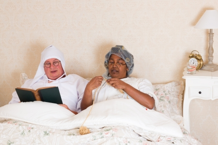 Elderly couple in vintage clothing reading and knitting in bed Stock Photo - 16305792