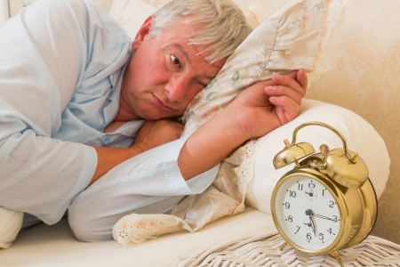 Sleepy elderly man waking up and looking at the alarm clock with one eye - focus is on the alarm clock photo