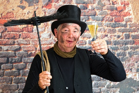 Happy chimney sweep toasting to the new year with a glass of champagne photo