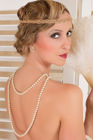 Vintage twenties lady with feather fan and pearls on nude back Stock Photo - 16412038