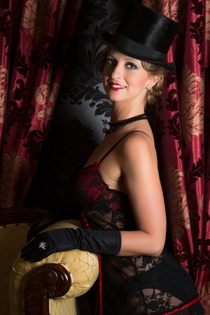 Seductive smiling woman in twenties vintage style with corset and top hat photo