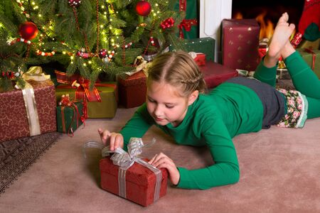 Young girl opening her present in front of the christmas tree photo