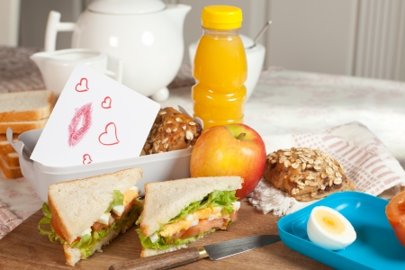 Little love note put into a lunchbox on the breakfast table photo