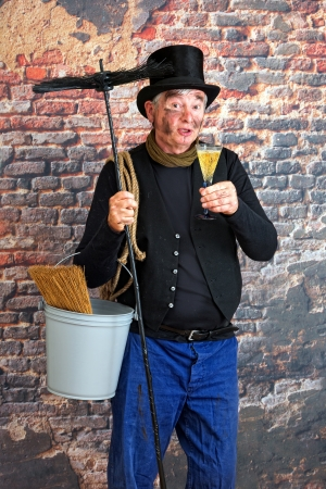 Smiling chimney sweep toasting to the new year with a glass of champagne photo