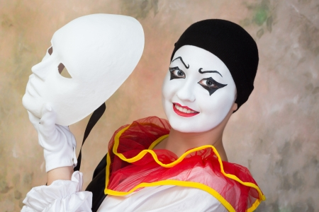 painted face mask: Female smiling pierrot holding a serious white face mask