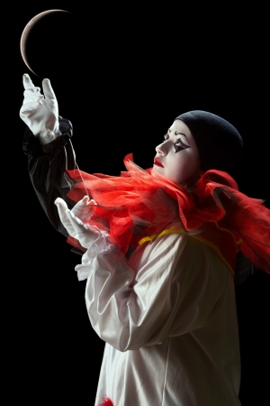 Beautiful Pierrot clown playing mime with the moon photo