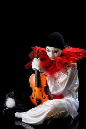 Sad Pierrot sitting on the floow with an old violin photo