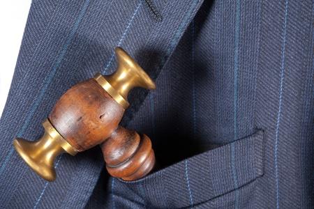 Judges hammer sitting in a pocket of a formal jacket