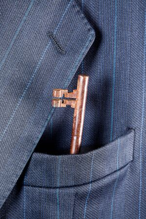 breast pocket: Rusty key in a breast pocket of a formal business suit