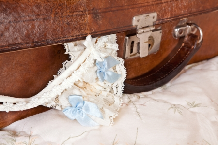 Wedding garter and bra straps hanging out of a vintage suitcase Stock Photo - 16557190
