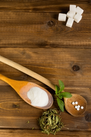 Dried and processed natural sweetener stevia together with real sugar lumps on a wooden table