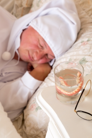 Vintage sleeping man in bed with his false teeth in a glass of water Stock Photo - 16672053