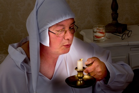 Vintage pensioner in nightclothes blowing out a candle Stock Photo - 16672055
