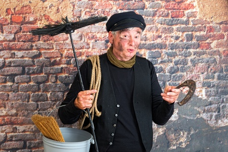 Chimney sweep wishing good fortune with a rusty horseshoe